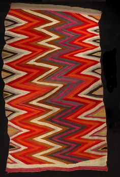 """Object Name: Blanket Origin: Navajo Reservation, Arizona-New Mexico Made: Navajo Description: Blanket made of hand spun wool, both warps and weft; wedge-weave (""""""""pulled warp"""""""") type; rectangular; colors include natural black and white, synthetic tan, red, rose, orange, yellow, and light blue-grey; design consists of multiple, overall, zig-zag stripes, vertically oriented; selvage cords are light orange. Materials: wool Repository: San Diego Museum of Man"""