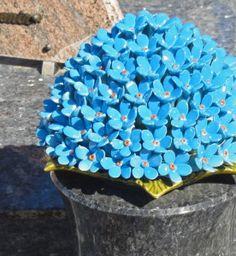 Ceramic flowers forget-me-nots Handmade and resistant to frost. They are handmade and resistant to frost. It is a French tradition to decorate gravesites with these ceramic flowers. Het is een Franse traditie om het graf te versieren met bloemen van keramiek. Hier zijn het vergeet mij nietjes.