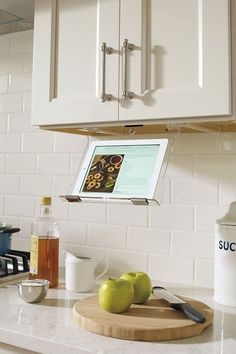 This iPad holder that's stored under the cabinet is perfect for when you're cooking and looking at online recipes! A must-have for our kitchen remodel! #kitchen #kitchens #cabinets