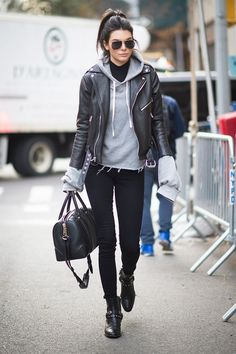 Kendall Jenner wears black skinny jeans, a raw cut gray hoodie, black leather moto jacket, studded ankle boots, and aviators.