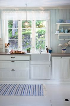 Beautiful kitchen features white shaker cabinets paired with calcutta marble countertops framing a stainless steel sink under three windows framed by white gloss mini subway tiled backsplash. Kitchen Sink Decor, Kitchen Sink Window, Tidy Kitchen, New Kitchen, Kitchen White, Kitchen Plants, Kitchen Ideas, Marble Countertops, Kitchen Countertops