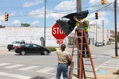Uncovering a stop sign.
