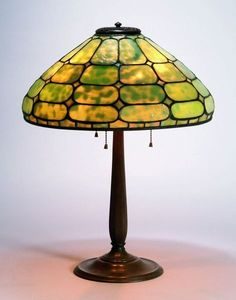 21½ inch Tiffany-signed Colonial bronze and glass table lamp, made sometime between 1902 and 1938, with a 12-paneled shade of heavily mottled green glass.