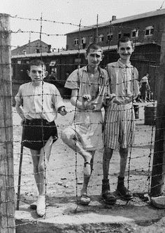 Young survivors behind a barbed wire fence in Buchenwald concentration camp.