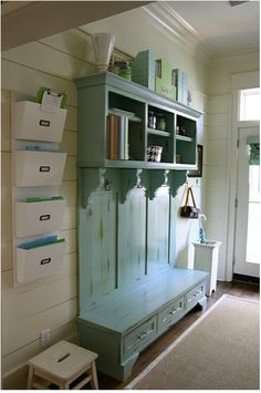 Mudroom-- it's so organized! I am really liking the icy light blue furniture piece against the creamy white wall.