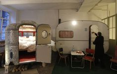 A caravan turned into sleeping accommodations is pictured in the indoor camping hotel Huettenpalast in Berlin,  200 square metre production hall of a small vacuum-cleaner factory was used to create an indoor garden where guests can sleep in old caravans and wooden huts.