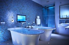 The bathroom features two, free-standing white volcanic limestone baths, separated by a Ch...