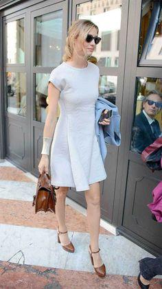 Beatrice, impecable con vestido de manga corta y sandalias y bolso marrrones, por las calles de Milán