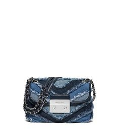 Denim on denim has never looked so chic. Our Sloan shoulder bag showcases frayed edges for an offbeat take on an opulent silhouette. Polished hardware and chain-and-leather straps finish this handbag with a fabulous touch.
