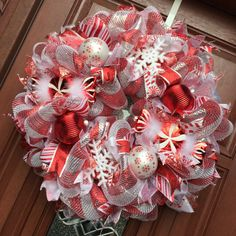 Candy canes are the theme of this fun and festive deco mesh holiday wreath; it was created with metallic red and silver candy cane striped deco