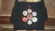 Bolsa em tamanho médio, feita com fio ecológico na cor preta. Detalhe de flores na frente. R$ 110,00