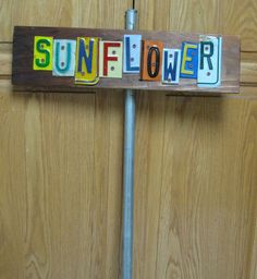 I made this plant marker from license plate letters, a piece of an old fence board, and a pipe from our pool demo. It's big, colorful, and will last a long time. License Plate Crafts, Old License Plates, License Plate Art, Licence Plates, Outdoor Crafts, Outdoor Projects, Diy Projects, Garden Junk, Garden Deco