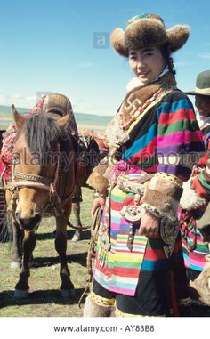 Tibetan Girl rider in a fur hat and traditional costume at Naqu Nagqu Horse Fair held annually in August in Northern Tibet Stock Photo