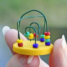 Dollhouse Miniature Toy Toddler Bead Maze. I could use polymer clay for a base, small colored beads and green ornament hooks.