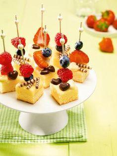 Kleine Stücke vom Käsekuchen mit fruchtigem Obst niedlich verziert
