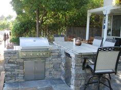I built this bar and bbq myself in the summer of 2006. The foundation is concrete block, with El Dorado stone for the facing. 4-burner stainless steel grill and a mini refrigerator. Countertops are ceramic tile on cement backerboard. The bar area is 4 inches higher than the grill area in order to have a distinct bar/serving area. The bbq/bar area took 3 months to plan and 1 month to build. It\'s been a great addition to our backyard.