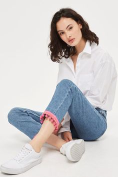 The must-have fit of the season, the MOTO straight leg jeans comes crafted in our authentic low stretch denim. In a comfortable mid-rise fit, they are cropped to the ankle with a tapered leg and pink pom pom hem detail.