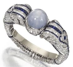 This is a very unusual Art Deco piece. It is a bracelet that reminds me the Cartier quimera ones from the same period. But this one is all platinum set with diamonds, featuring two elephant heads that hold a large cabochon star sapphire.