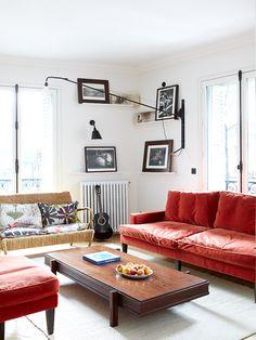 modern white living room with black framed art prints and red velvet sofa…