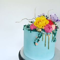 Boho buttercream cake in turquoise with bright floral bouquet and gold drip