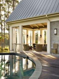 Cottage home features a circular in-ground pool next to a covered deck filled with wicker ...