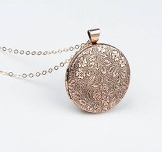 Your choice of gorgeous floral antiqued rose gold or shiny silver locket necklace. These beauties are perfectly mid sized. Great for picture mementos to feature a special occasion or loved one. Antiqued paisley flower detail on the front is repeated on the back side. Two removable metal