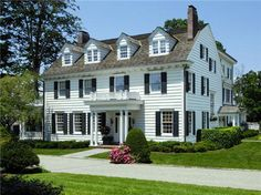 Classic new england home, cedar shingle roof, black shutters, white siding.