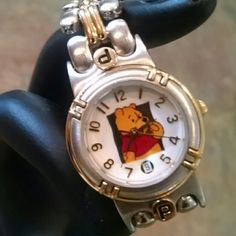 """Winnie the Pooh watch Brushed silver and gold band, I'm guessing it is stainless steel.  Links CANNOT be removed!! I did bring it to a jeweler once to be sized and that is what I was told I wear a 7.5"""" bracelet, this watch fits me comfortably with slight movement Needs a battery Disney Jewelry"""