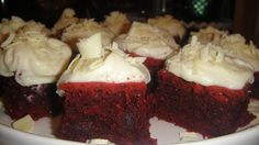 Homemade red velvet brownies with cream cheese icing and shaved white chocolate.