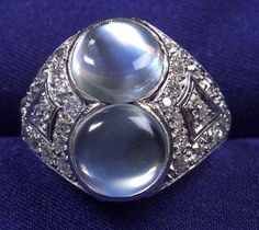 Platinum, Moonstone, and Diamond Ring, centering two moonstone cabochons, within a pierced mount bead-set with old European-cut diamond melee.