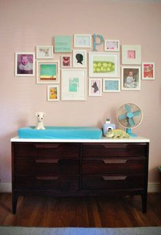 Nursery wall. I have this exact same setup of pics/art in my living room, but I love how there are old baby pics of parents, a cameo, & a letter in the mix. So cute!!!