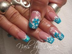 Blue glitter french tips on nude nails with free hand blue flowers white detail & polka dots nail art