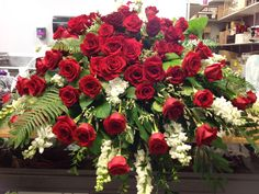 beautiful floral tribute of red roses and snapdragons for a loved one