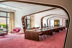 Library in the new offices of Dropbox in San Francisco, CA. The soft pink carpet is borrowed from the European opera houses, and the long, walnut tables feature Kennedy style desk lamps showing mid-century design. [1500 × 1000]