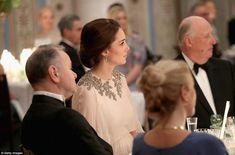 The Duchess, who is wearing a dusty pink dress with a detailed neckline and matching drop earrings, appeared to listen intently to the next dinner speaker