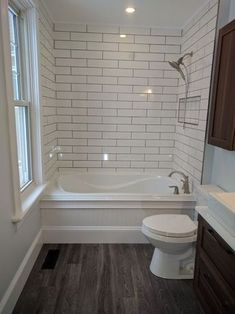 """Transitional style bathroom remodel with 4""""x16"""" Subway Tile, drop-in tub with custom wainscoting #transitionalstyle #bathroom #remodel #subwaytile #kimberley #fernie #cranbrook #bathtubwainscoting"""