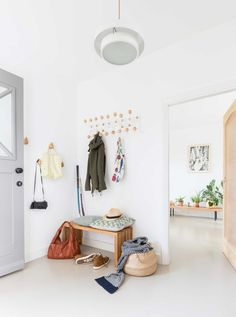 The entryway is Scandinavian, all white with light colored wood touches