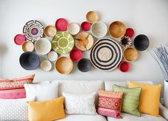 Baskets A cluster of colorful baskets is a great way to spice up a plain white wall. Particularly striking in this modern interior, an arrangement of beautiful, tactile baskets adds a bit of old-world charm. To create this look yourself, select baskets of different sizes and colors, and attach them to the wall with hidden screws or hooks.