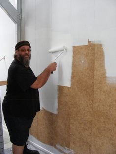 Augur from the Henderson Community Men's Shed helps out with the painting at the North Shore Men's Shed.