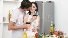 Couple drinking wine and eating salad in the kitchen - Stock Footage | by seanp