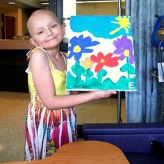 """A cancer patient at Dayton Children's smiles with one of her """"masterpieces."""""""