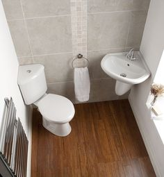 A Small Bathroom With A Corner Toilet