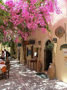 A street scene with the bouganvillea vines in bloom, Rethymno, Crete, Greece