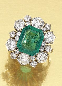 EMERALD AND DIAMOND RING.  Design as a cluster centring on a cut-cornered step-cut emerald, within surrounds of brilliant-cut diamonds