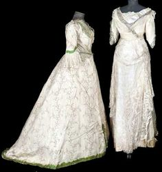 "Two gowns from the late 19th/early 20th centuries. On the left: cream-colored silk embroidered with apple green and white orange blossoms and with green silk embellishment. The skirt is very full. On the right: a white silk chiffon evening gown with silver bead trim and blonde lace. It is labelled ""Madame Lillian, Notting Hill Gate."""