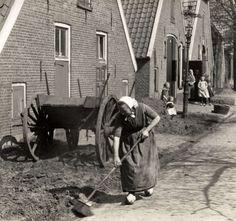 Klederdrachten. Vrouw in klederdracht is voor het huis het straatje aan het vegen. In de voortuin een boerenkar. Rijssen, Overijsel, Nederland, 1925. Serie van 2 fotos.