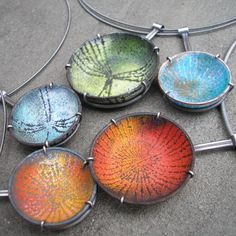 "Raised copper ""bowls"" with enamel and hand fabricated prong cages in sterling."