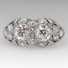 This beautiful antique ring features lovely filigree and milgrain details and dates from the 1920's. The large twin diamonds are old European cuts and there are 12 additional smaller old European diamonds encrusting the mounting.  This ring is made of platinum and the craftsmanship that went into it is remarkable. The shank was replaced with a thicker 19k white gold shank sometime more recently. One of the main diamonds and one of the accent diamonds is chipped, but nothing distracting. C...