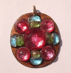 "Ruth Buol vintage copper enamel and fused glass pendant - the pendant features a light brown enamel background with applied pink, light blue, and light green glass pieces. It measures approx 2 1/4"" x 2"" and is signed ""BUOL"" on the underside(the piece also retains its original labels)."