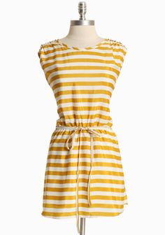 Luminescent faux pearls shimmer and dance with every movement on this silky ivory and mustard striped dress.